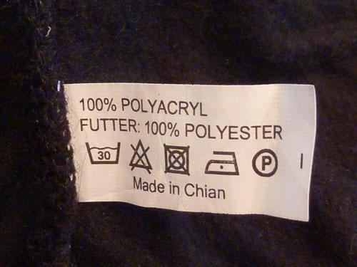 Der Druckfehler deutet auf eine Fälschung hin. Vermutlich ist die Mütze aus reiner Baumwolle.